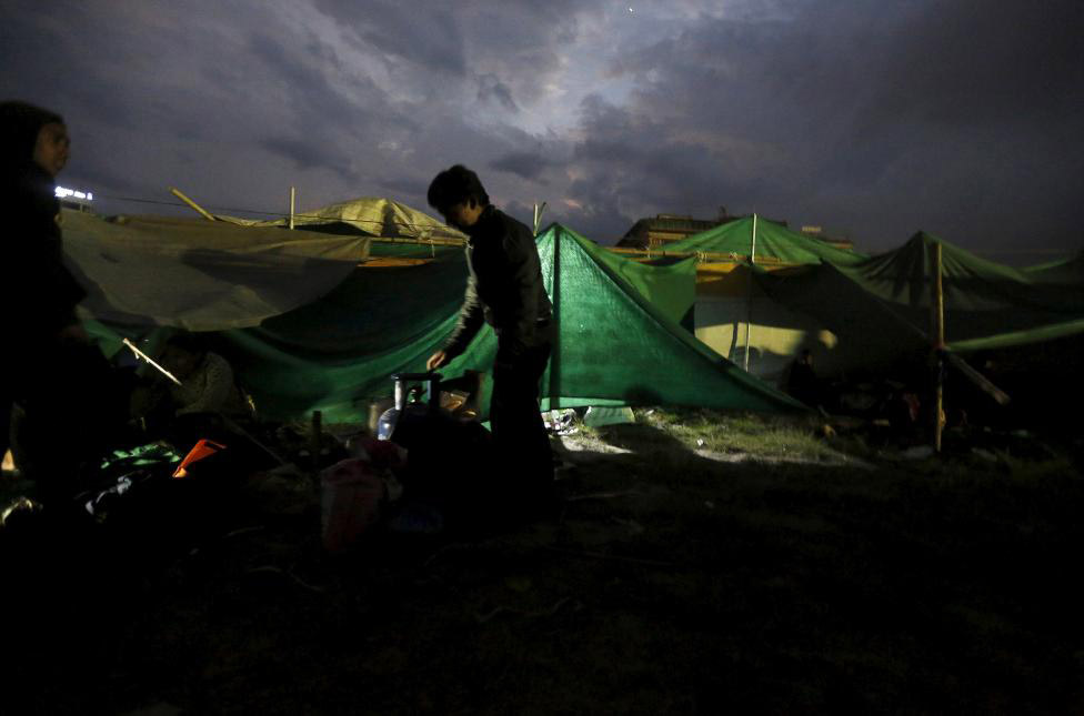 A boy prepares to cook food outside a makeshift shelter on open ground in Kathmandu