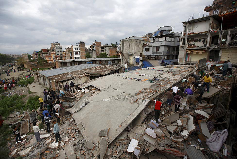 People gather near a collapsed house in Kathmandu