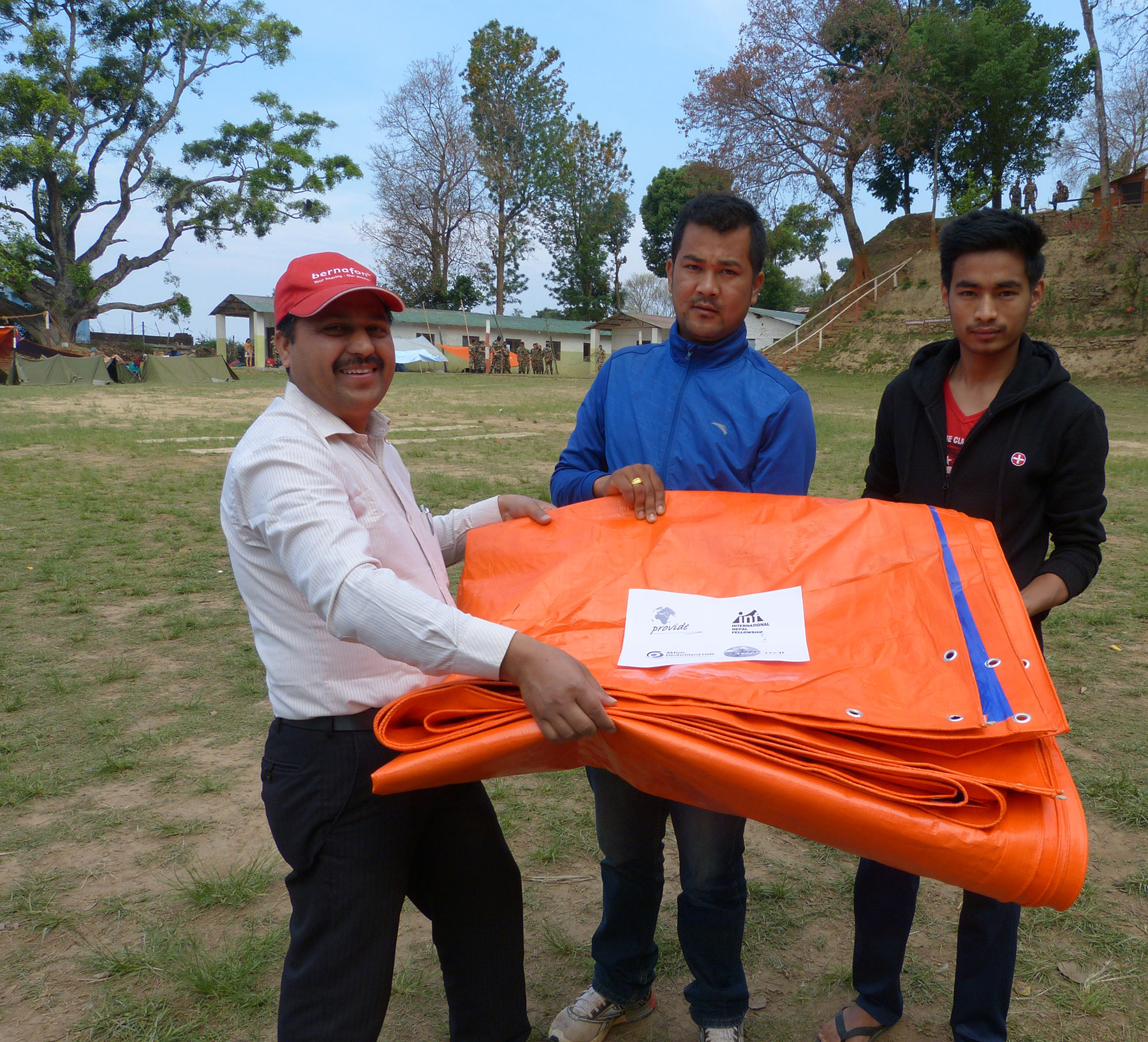 Handing over tarpaulins to people who have lost their home