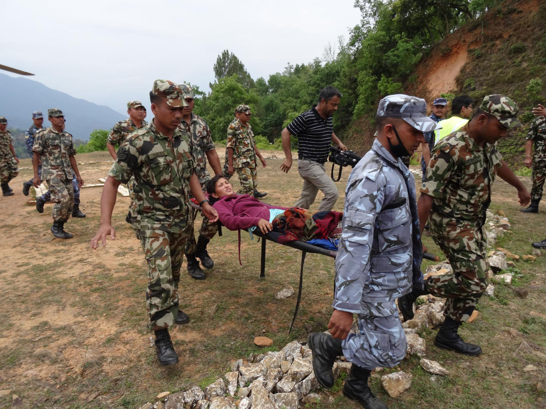 Injured woman carried out on stretcher by army and police