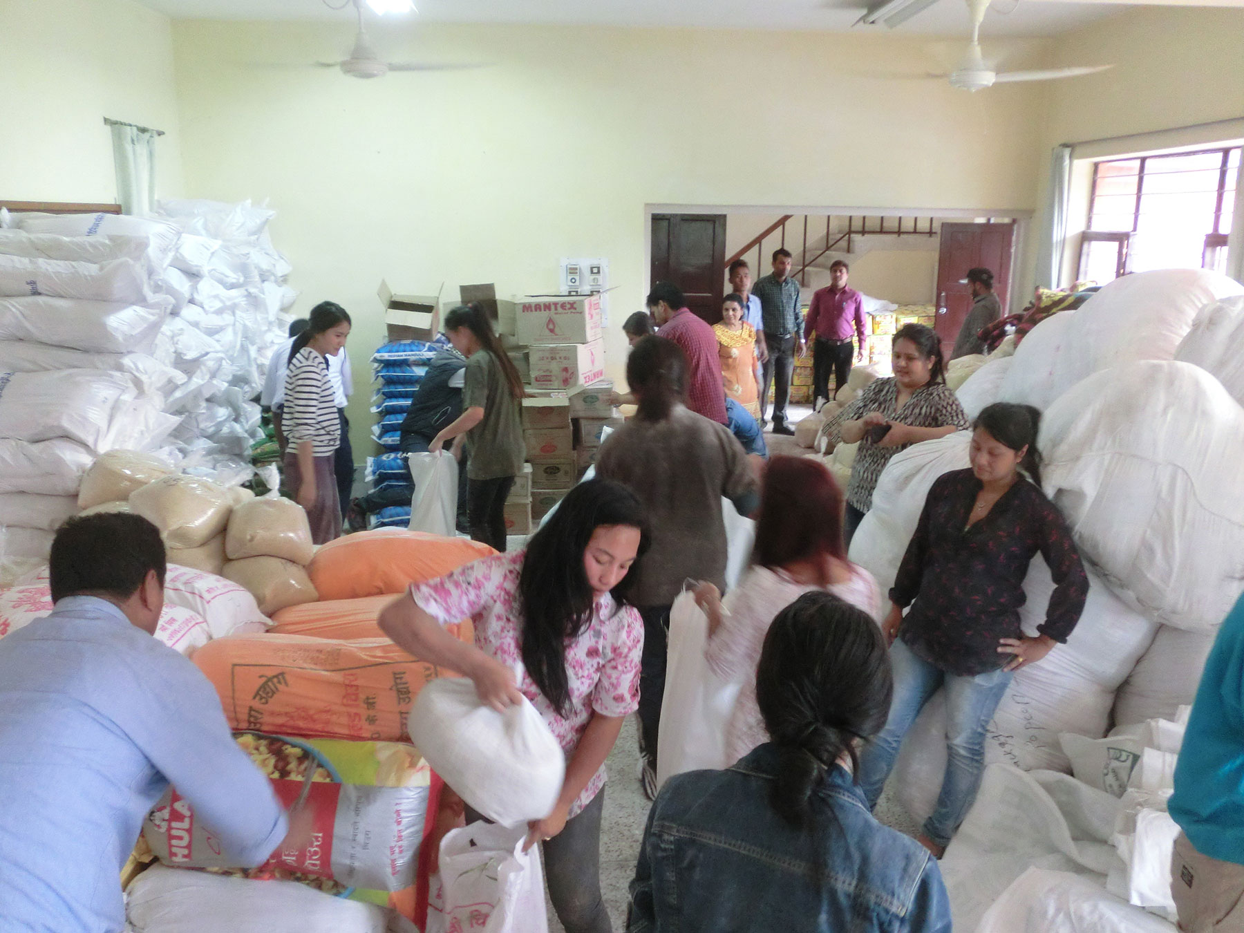 Preparing sacks of rice and lentils for distribution
