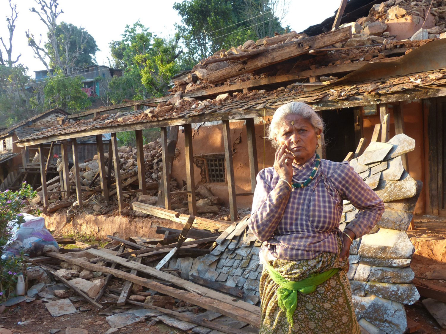 Woman outside her collapsed home